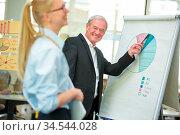 Alter Geschäftsmann zeigt auf Diagramm an einem Flipchart während... Стоковое фото, фотограф Zoonar.com/Robert Kneschke / age Fotostock / Фотобанк Лори