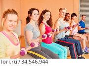 Leute heben Gewichte mit Hanteln im Fitnesscenter. Стоковое фото, фотограф Zoonar.com/Robert Kneschke / age Fotostock / Фотобанк Лори