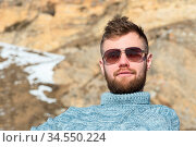 Portrait of a traveler's Hipster in sunglasses and a knitted gray... Стоковое фото, фотограф Zoonar.com/Ian Iankovskii / easy Fotostock / Фотобанк Лори