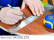 Close-up Men's hands draw a pencil on the ruler with a sub-standard... Стоковое фото, фотограф Zoonar.com/Ian Iankovskii / easy Fotostock / Фотобанк Лори