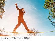 A man, aged with a beard and wearing sunglasses, balances on a slackline... Стоковое фото, фотограф Zoonar.com/Ian Iankovskii / easy Fotostock / Фотобанк Лори