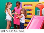 Drei Mädchen spielen ein Klatschspiel mit den Händen zusammen im ... Стоковое фото, фотограф Zoonar.com/Robert Kneschke / age Fotostock / Фотобанк Лори