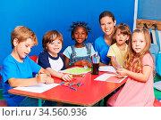 Viele Kinder zeichnen zusammen im Kindergarten am Tisch mit einer... Стоковое фото, фотограф Zoonar.com/Robert Kneschke / age Fotostock / Фотобанк Лори