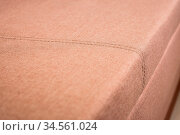 A close-up of a fragment of an expensive beige textile sofa in the... Стоковое фото, фотограф Zoonar.com/Ian Iankovskii / easy Fotostock / Фотобанк Лори