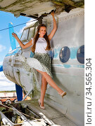Pleasant young woman standing on the wing of an abandoned plane. Стоковое фото, фотограф Алексей Кузнецов / Фотобанк Лори