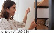 woman decorating home with garland lights. Стоковое видео, видеограф Syda Productions / Фотобанк Лори