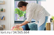 woman placing flowers on coffee table at home. Стоковое видео, видеограф Syda Productions / Фотобанк Лори