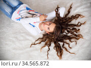 Portrait of a pretty teen girl lying on the floor with her long hair. Стоковое фото, фотограф Nataliia Zhekova / Фотобанк Лори