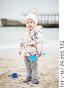 Little girl playing on the sandy beach. Happy child wearing warm floral print jacket, pom pom hat and scarf playing outdoors on fall, winter or spring day. Стоковое фото, фотограф Nataliia Zhekova / Фотобанк Лори