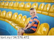 Little boy sitting in an empty stadium among yellow plastic numbered seats and applauds. Стоковое фото, фотограф Nataliia Zhekova / Фотобанк Лори