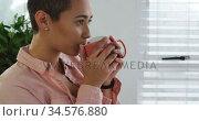 Woman having a coffee at window. Стоковое видео, агентство Wavebreak Media / Фотобанк Лори