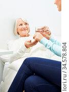 Seniorin im Bett nimmt Medizin mit Wasser ein in einem Pflegeheim. Стоковое фото, фотограф Zoonar.com/Robert Kneschke / age Fotostock / Фотобанк Лори