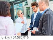 Gruppe Geschäftsleute beim Smalltalk in einer Kaffeepause vor dem Büro. Стоковое фото, фотограф Zoonar.com/Robert Kneschke / age Fotostock / Фотобанк Лори