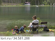 Mere et enfants au bord du Lac de Dobbiaco, Region du Trentin-Haut... Редакционное фото, фотограф Christian Goupi / age Fotostock / Фотобанк Лори