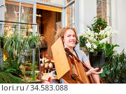 Junger Florist als Azubi mit Blume und Leiter vor dem Blumenladen. Стоковое фото, фотограф Zoonar.com/Robert Kneschke / age Fotostock / Фотобанк Лори