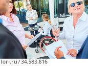 Behinderte Geschäftsfrau im Rollstuhl beim Smalltalk mit Kollegen... Стоковое фото, фотограф Zoonar.com/Robert Kneschke / age Fotostock / Фотобанк Лори