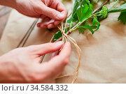 Hände von Florist beim Blumen binden mit Bast macht eine Schleife. Стоковое фото, фотограф Zoonar.com/Robert Kneschke / age Fotostock / Фотобанк Лори