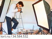 Foodfotograf mit Kamera bei Fotoshooting im Studio auf einer Leiter. Стоковое фото, фотограф Zoonar.com/Robert Kneschke / age Fotostock / Фотобанк Лори