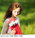 Girl holding a plastic skate board outdoors. Стоковое фото, фотограф Nataliia Zhekova / Фотобанк Лори