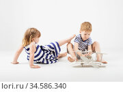 Little Children playing with paper toy airplane sitting on the floor against a white background. Стоковое фото, фотограф Nataliia Zhekova / Фотобанк Лори