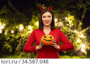 woman in halloween costume of devil with pumpkin. Стоковое фото, фотограф Syda Productions / Фотобанк Лори
