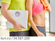 close up of woman and man with scales in gym. Стоковое фото, фотограф Syda Productions / Фотобанк Лори