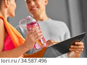 woman with water bottle and trainer in gym. Стоковое фото, фотограф Syda Productions / Фотобанк Лори
