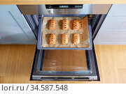 baking tray with jam pies in oven at home kitchen. Стоковое фото, фотограф Syda Productions / Фотобанк Лори