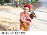 Little urban boy with a penny skateboard. Kid skating in a summer park. City style. Urban kids. Стоковое фото, фотограф Nataliia Zhekova / Фотобанк Лори