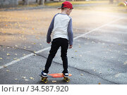 Little urban boy with a penny skateboard. Young kid riding in the park on a skateboard. City style. Urban kids. Стоковое фото, фотограф Nataliia Zhekova / Фотобанк Лори