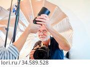 Professioneller Fotograf bekommt Hilfe beim Objektivwechsel an Kamera. Стоковое фото, фотограф Zoonar.com/Robert Kneschke / age Fotostock / Фотобанк Лори