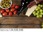 view of a composition with pieces of bread, cheese, sausage, fresh fruits and a bottle of wine on wo. Стоковое фото, агентство Wavebreak Media / Фотобанк Лори