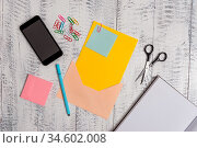 Envelope sheet smartphone notes pen notepad clips scissors wooden back. Стоковое фото, фотограф Zoonar.com/Artur Szczybylo / easy Fotostock / Фотобанк Лори