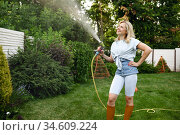 Smiling woman with hose watering trees in garden. Стоковое фото, фотограф Tryapitsyn Sergiy / Фотобанк Лори