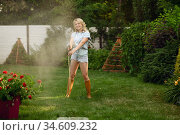 Gardener with hose watering plants in the garden. Стоковое фото, фотограф Tryapitsyn Sergiy / Фотобанк Лори