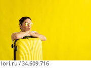 A woman in sunglasses hugs a suitcase on a yellow background. Стоковое фото, фотограф Михаил Решетников / Фотобанк Лори