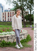 Full length portrait of pre-teen Caucasian girl wearing beige blouse and grey breeches stands outdoor, posing for camera. Стоковое фото, фотограф Кекяляйнен Андрей / Фотобанк Лори