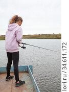 Pre-teen girl standing with fish rod, female fisherman catching the fishes from pier. Стоковое фото, фотограф Кекяляйнен Андрей / Фотобанк Лори