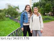 Pre-teen schoolgirl in grade 6 goes back to school at September with her mother, together portrait outdoor. Стоковое фото, фотограф Кекяляйнен Андрей / Фотобанк Лори