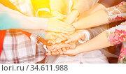 Viele Schüler stapeln zusammen ihre Hände zur Motivation in der Schule. Стоковое фото, фотограф Zoonar.com/Robert Kneschke / age Fotostock / Фотобанк Лори