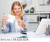 Business woman sitting giving white sticker. Стоковое фото, фотограф Яков Филимонов / Фотобанк Лори