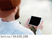 Hipster person holding in hands digital tablet with empty blank screen... Стоковое фото, фотограф Zoonar.com/Ian Iankovskii / easy Fotostock / Фотобанк Лори