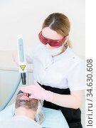The cosmetician girl in goggles makes the procedure of carbon peeling... Стоковое фото, фотограф Zoonar.com/Ian Iankovskii / easy Fotostock / Фотобанк Лори