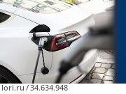 Power supply for electric car charging. Electric car charging station. Close up of the power supply plugged into an electric car being charged. Стоковое фото, фотограф Matej Kastelic / Фотобанк Лори
