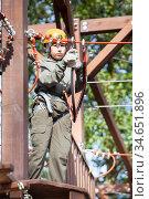 Preteen Caucasian girl climbs on rope course wearing climbing equipment. Стоковое фото, фотограф Кекяляйнен Андрей / Фотобанк Лори