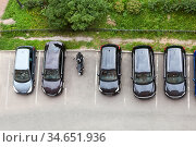 Line from parked cars and one motorcycle standing on parking place for vehicle, top view. Стоковое фото, фотограф Кекяляйнен Андрей / Фотобанк Лори