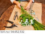 Hände einer Floristin beim Blumen binden mit Bast für einen Blumenstrauß. Стоковое фото, фотограф Zoonar.com/Robert Kneschke / age Fotostock / Фотобанк Лори
