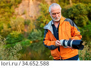 Professioneller Naturfotograf mut Superzoom Objektiv in der Natur. Стоковое фото, фотограф Zoonar.com/Robert Kneschke / age Fotostock / Фотобанк Лори