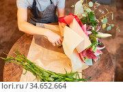 Hände von Florist beim Blumen binden und in Papier einwickeln. Стоковое фото, фотограф Zoonar.com/Robert Kneschke / age Fotostock / Фотобанк Лори