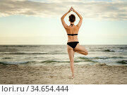 Beautiful woman in a black swimsuit practicing yoga on the beach at... Стоковое фото, фотограф Michal Jerzy Oska / easy Fotostock / Фотобанк Лори